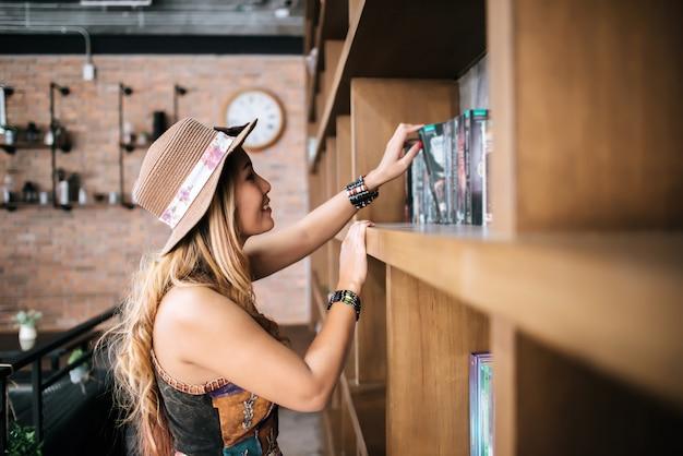 Молодая девушка берет книгу с полки, в библиотеку