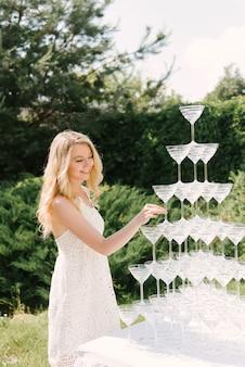 Молодая девушка берет бокал из пирамиды шампанского, фуршет на свежем воздухе