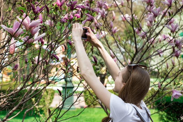 Young girl takes pictures of flowering tree. mobile photography.