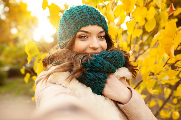 Young girl takes a selfie on the backgroung autumn beautiful leaves.