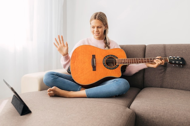 Молодая девушка берет урок игры на гитаре онлайн