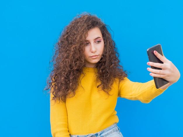 Молодая девушка фотографирует себя