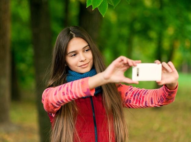 Молодая девушка, делающая селфи со смартфоном