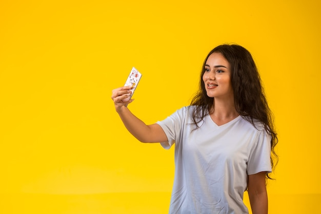 Ragazza che prende il suo selfie sul telefono cellulare sulla parete gialla.
