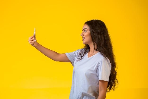 黄色の背景の携帯電話で自分撮りを取り、前向きに笑って、縦断ビュー。