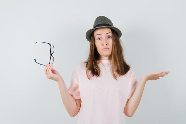 ピンクのtシャツ、帽子、無力に見える、正面図で眼鏡を脱いで若い女の子。