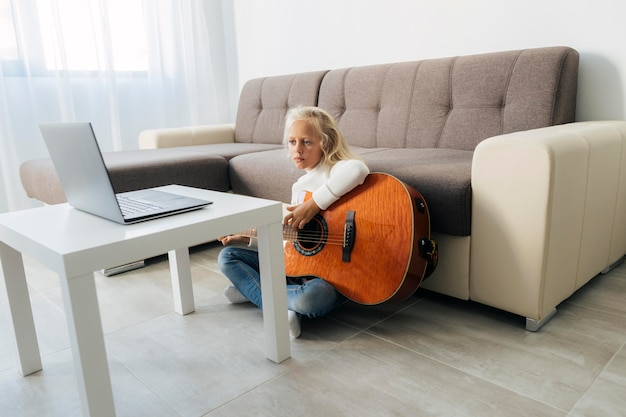 Young girl taking an online guitar lesson