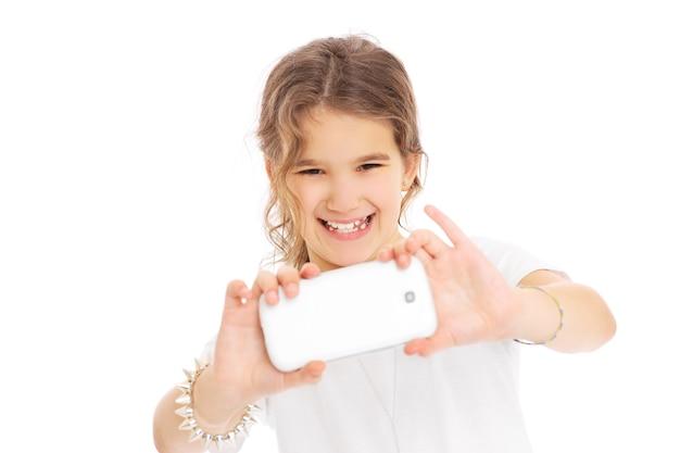 Молодая девушка фотографирует на белом фоне