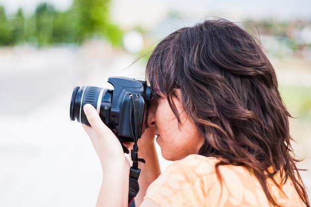 Молодая девушка фотографировать с зеркальной камерой