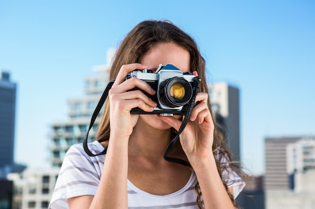 Young girl taking photos in town in a sunny day