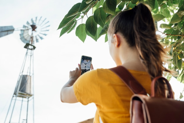 Young girl taking a picture of a windmill
