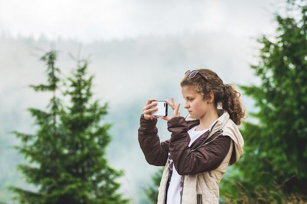Молодая девушка фотографирует горы