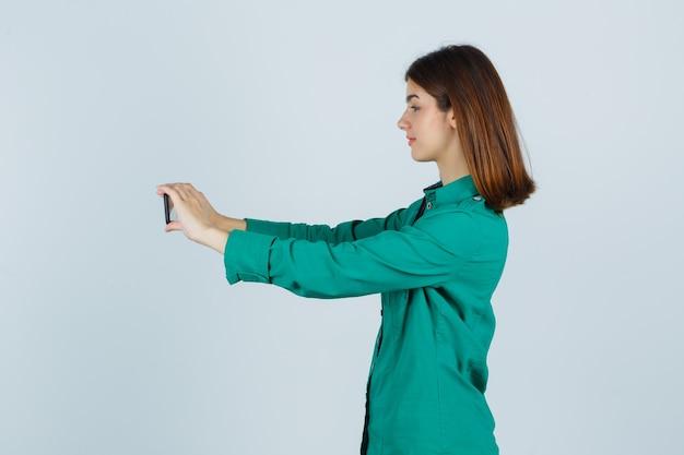 Ragazza che cattura selfie in camicetta verde, pantaloni neri e guardando concentrato. vista frontale.