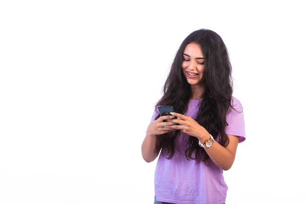 Ragazza che cattura selfie o effettua una videochiamata su sfondo bianco e sembra positiva.