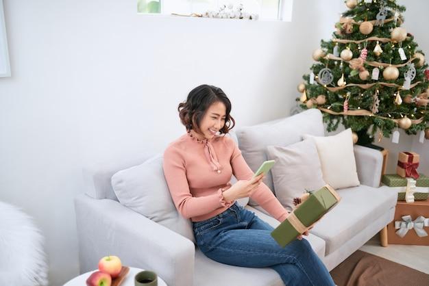 소파에서 셀카를 찍는 어린 소녀. 휴대폰 친구에게 선물을 보여주는 귀여운 크리스마스 소녀.