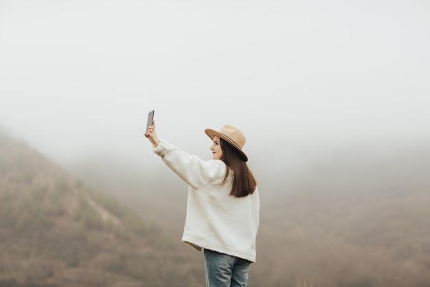 안개가 하루에 산에서 야외에서 selfie를 복용하는 어린 소녀.