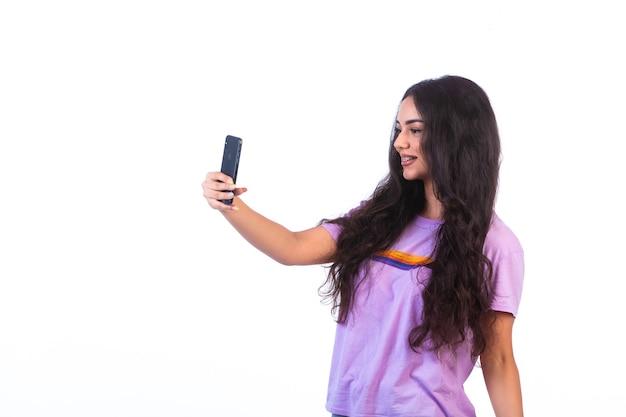 白い背景の上の彼女の携帯電話でselfieを取っている若い女の子