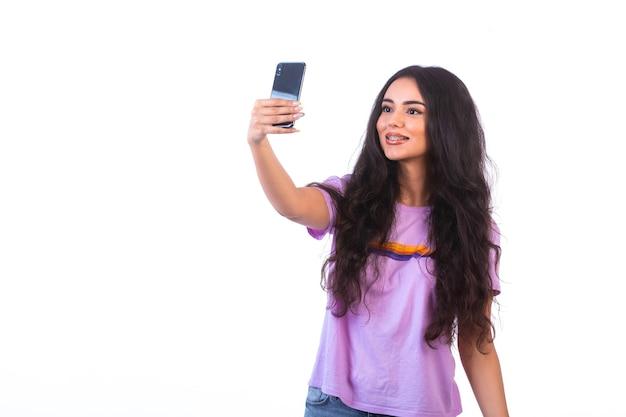 Ragazza che cattura selfie con il suo telefono cellulare sul muro bianco.