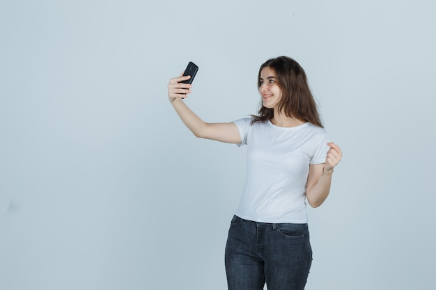 Ragazza che cattura selfie con il telefono cellulare in t-shirt, jeans e cerca affascinante, vista frontale.