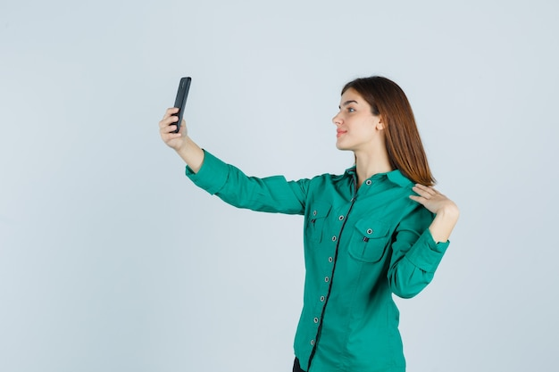 Young girl taking selfie with phone in green blouse, black pants and looking happy , front view.