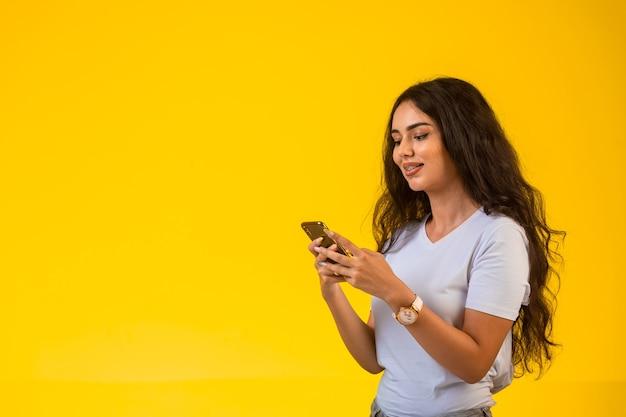 Молодая девушка разговаривает и болтает по телефону, улыбаясь