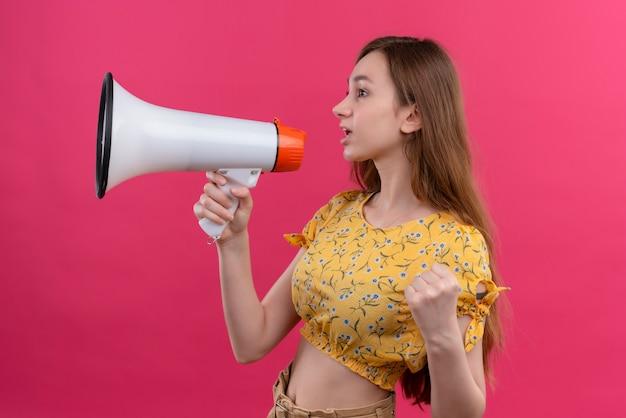 Ragazza che parla dall'altoparlante e che alza il pugno che sta nella vista di profilo sulla parete rosa isolata