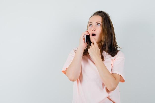 Молодая девушка разговаривает по мобильному телефону в розовой футболке и выглядит задумчиво