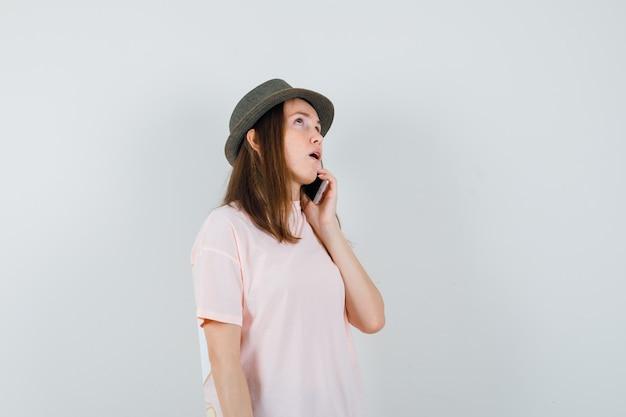 Молодая девушка разговаривает по мобильному телефону в розовой футболке, шляпе и задумчиво, вид спереди.