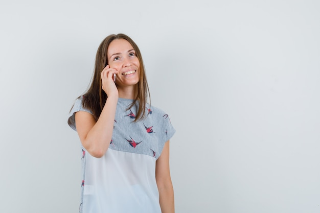 Молодая девушка разговаривает по мобильному телефону в футболке и рад, вид спереди.