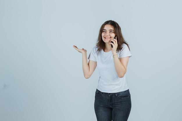 Молодая девушка разговаривает по мобильному телефону, делая вид, что держит что-то в футболке, джинсах и выглядит радостной. передний план.