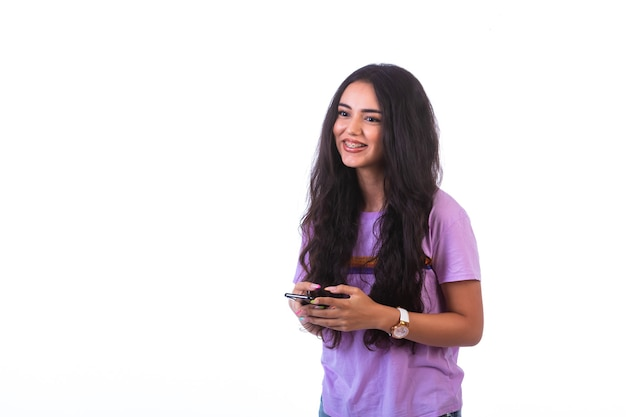 Молодая девушка разговаривает онлайн с друзьями и улыбается.