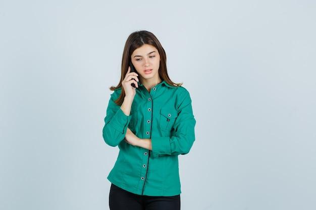 Ragazza che parla al telefono, guardando in basso in camicetta verde, pantaloni neri e guardando concentrato, vista frontale.