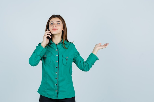 Young girl talking to phone, spreading palm aside in green blouse, black pants and looking happy , front view.