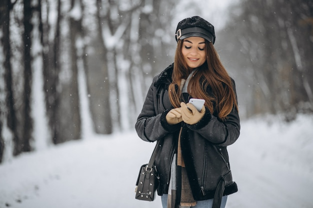 Young girl talking on the phone in a winter park