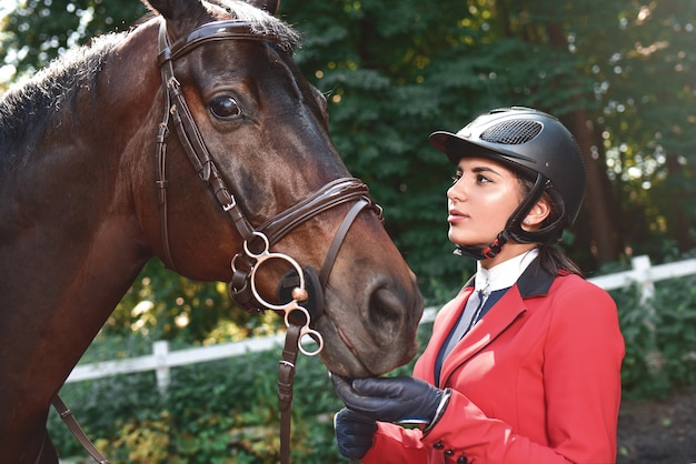 A young girl talking and takes care of her horse. she loves the animals and joyfully spends her time in their environment.