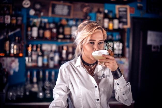 若い女の子のタプスターは、カクテルバーで飲み物の最後の仕上げをします