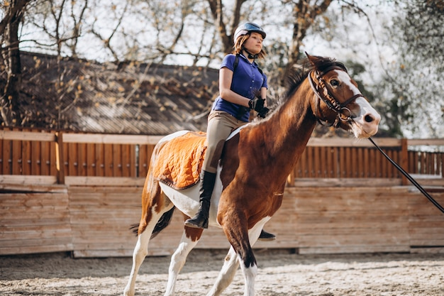 Young girl teaching horse riding