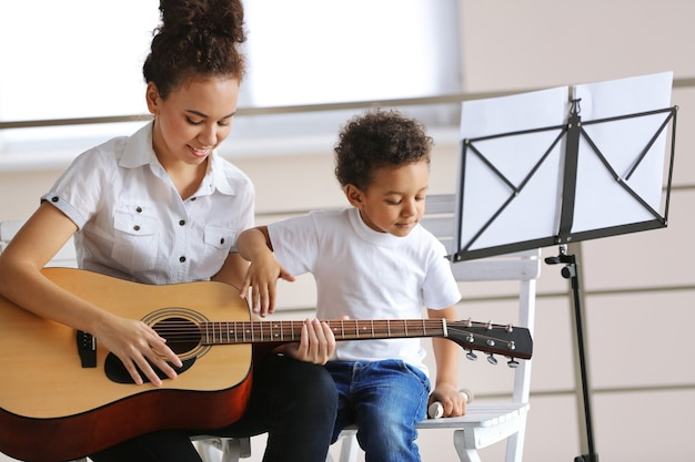 小さな男の子にギターを弾くように教える少女