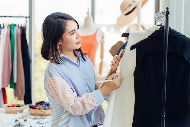 若い女の子の十代のファッションショップ中小企業の経営者が新製品の注文のために在庫をチェックしています
