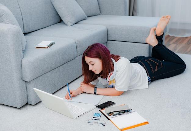Молодая девушка на полу с помощью ноутбука