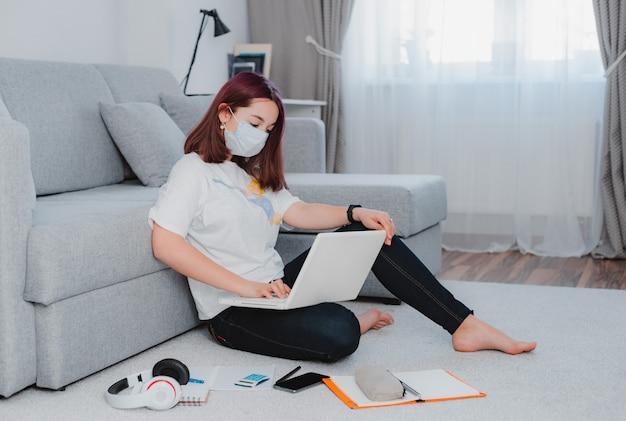 Молодая девушка девушка на полу в защитной маске с помощью ноутбука