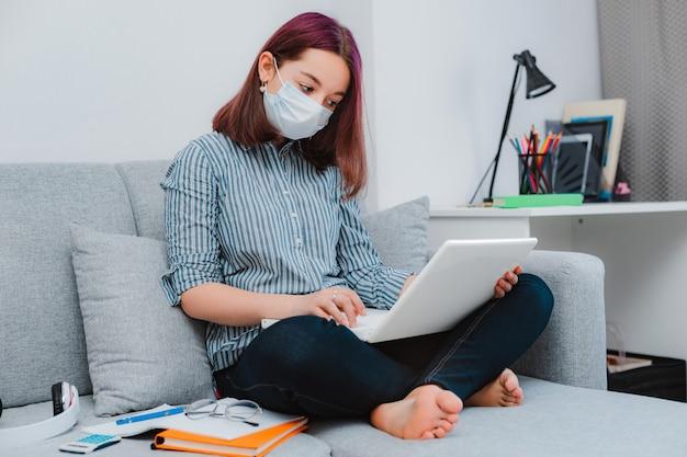 Молодая девушка девушка на диване в защитной маске с помощью ноутбука