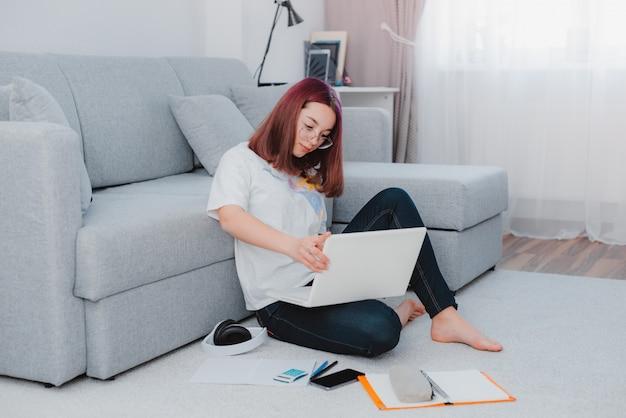 Молодая девушка подростковой школьница, сидя на полу, с помощью ноутбука