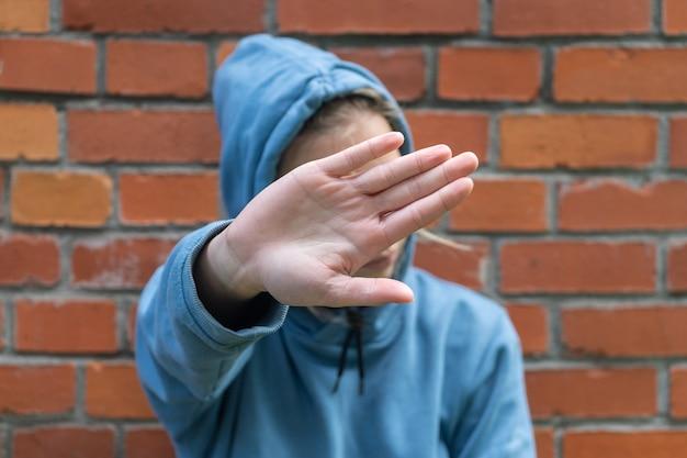 Молодая девушка, подросток закрывает лицо рукой. юношеское смущение, отказ от общения.