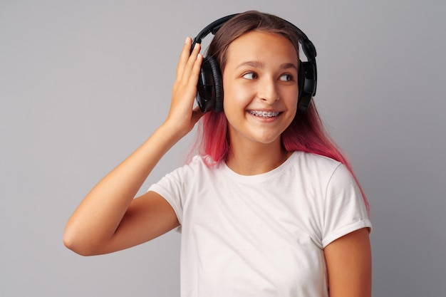 Young girl teenager listening to music with her headphones over a grey