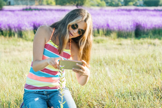 Young girl teenager walking in nature photographs flower plant on mobile smartphone