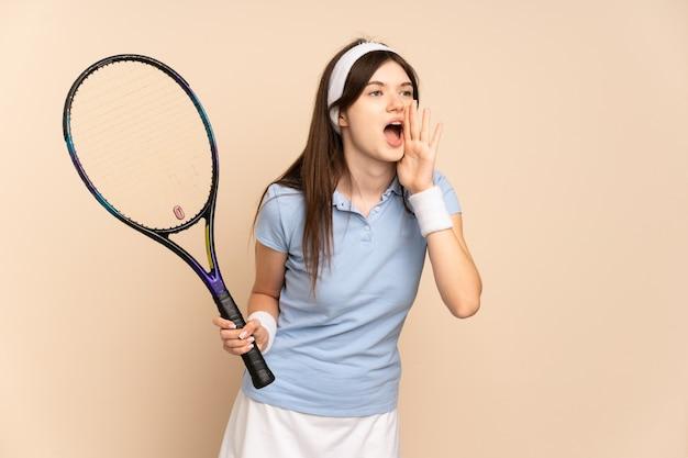 Молодая девушка-теннисистка над изолированной стеной кричит с широко открытым ртом в сторону