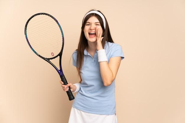 Молодая девушка-теннисистка над изолированной стеной кричит с широко открытым ртом