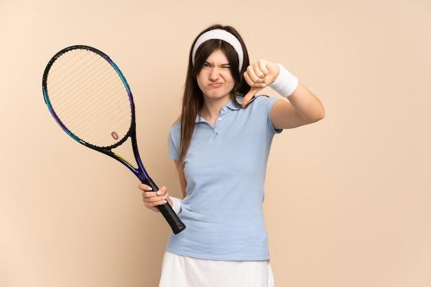 Молодая девушка-теннисистка над изолированной стеной показывает большой палец вниз с отрицательным выражением лица