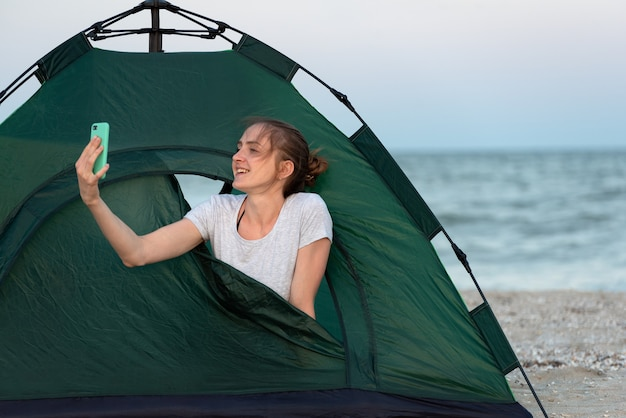 Young girl in tent on sandy beach against sea background. using her mobile phone.